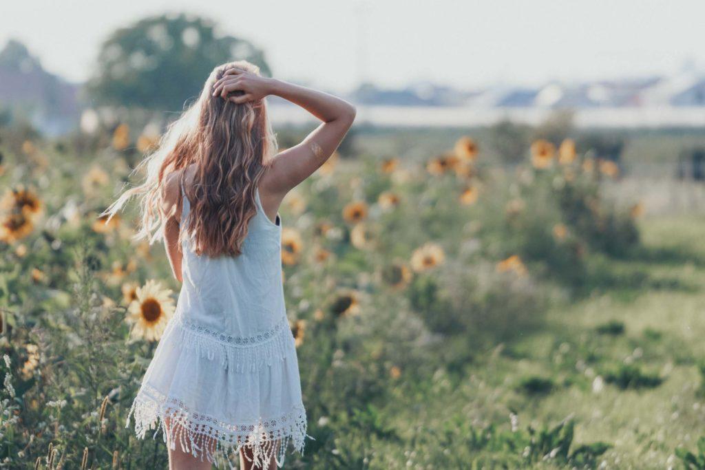 Blondes Mädchen im weißen Kleid in einem Sonneblumenfeld