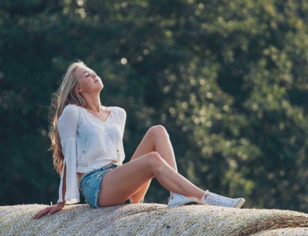 Hannah in der Abendsonne auf einem Strohballen sitzend