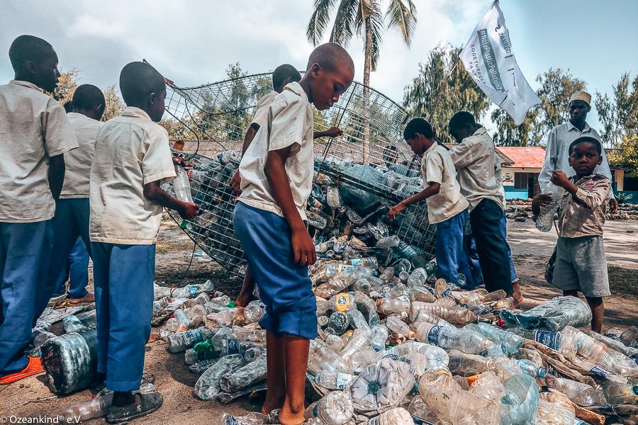 Junge Afrikaner beim Sammeln von Plastikmüll am Strand